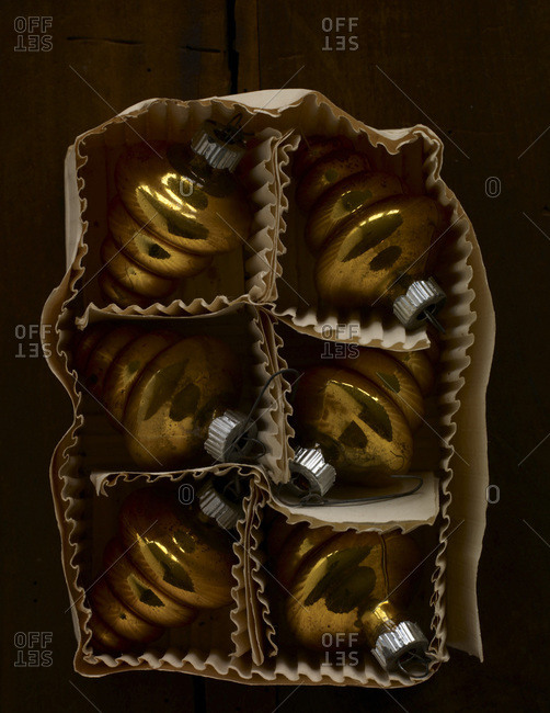 Handmade golden christmas ornaments in a paper box.