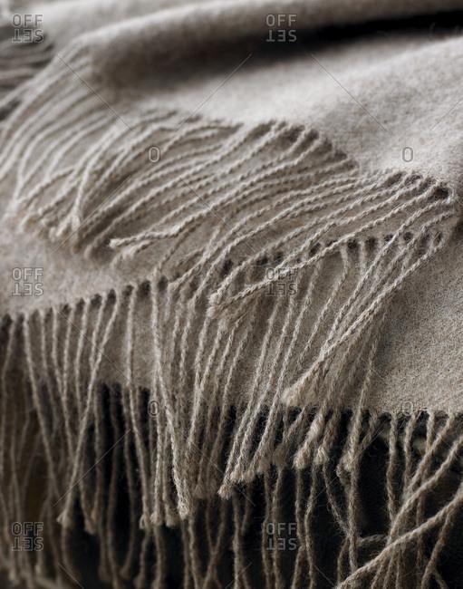 Fringes of a light brown cashmere blanket.