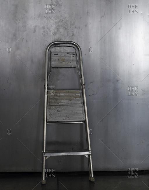Metal ladder against a metal wall