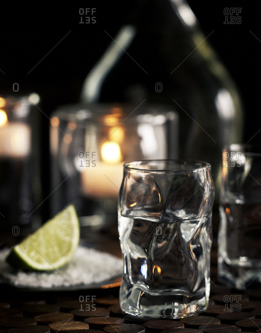A glass of tequila with a lime wedge and salt on a bar counter.