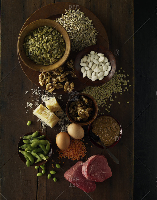 Protein-rich oilseeds, cheese and raw meat on a wooden table from above.