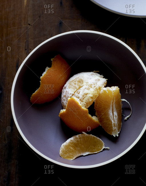 Peeled tangerine segments in bowl.