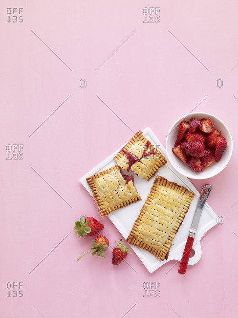 Cookies filled with jam and with fresh strawberries in bowl.