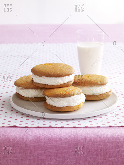 Plate of cream stuffed cookies with a glass of milk.
