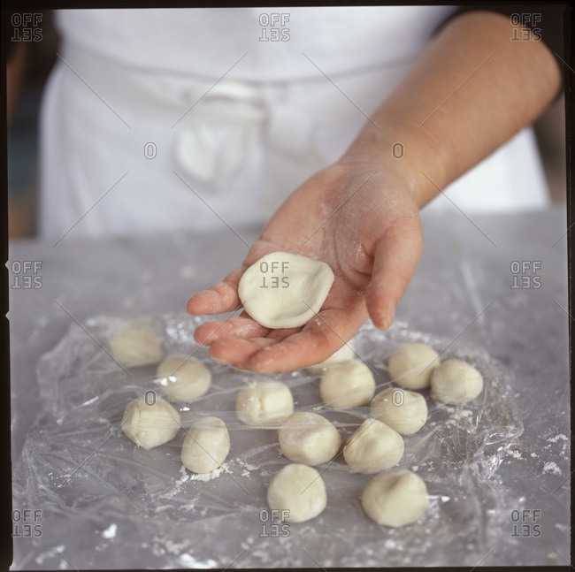 One raw dumpling in hand and several on the table covered by clingfilm.