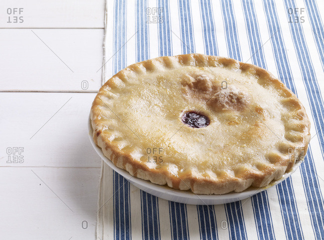 Golden brown fruit pie on plate.