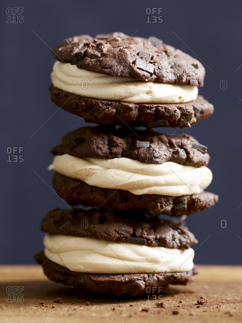 Close up of three chocolate cookies arranged on each other.