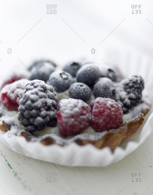 Close up of a fruit tart topped with fresh berries.
