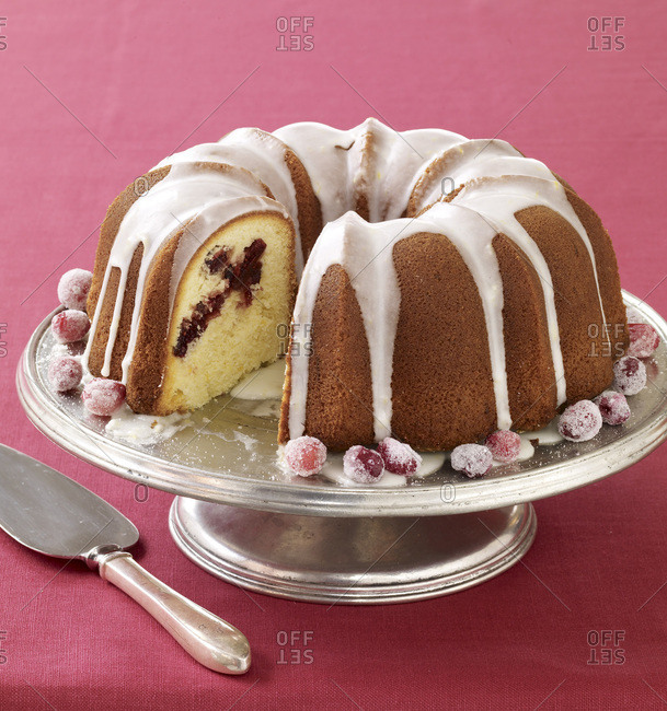 Glazed bundt cake with fruits on a cake stand.