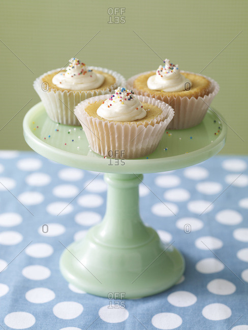 Three cupcakes with sprinkles on a cake holder.