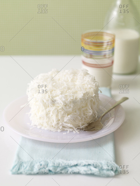 Delicious coconut cake and a glass of milk in the background.