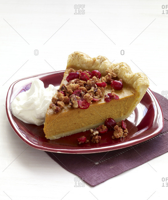 Piece of pumpkin pie sprinkled with fruits and nuts and with whipped cream.