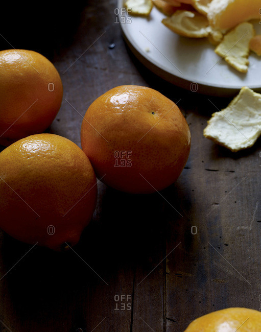 Tangerines on a table with peels and segments in the background.