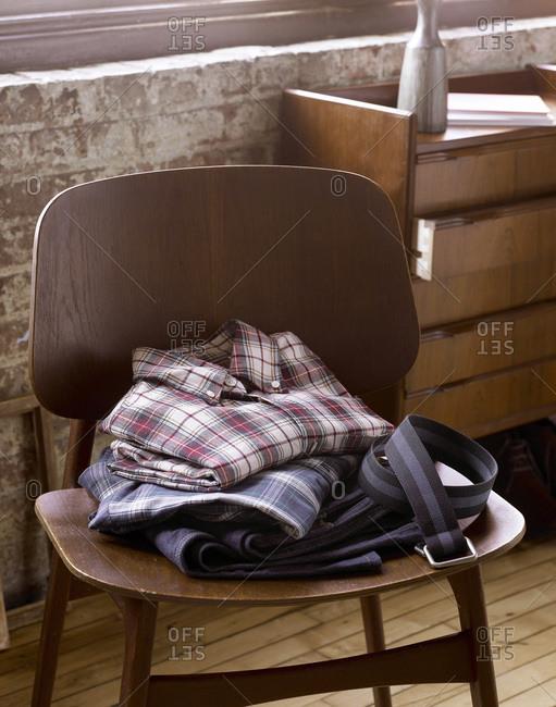 Folded menswear on a wooden chair