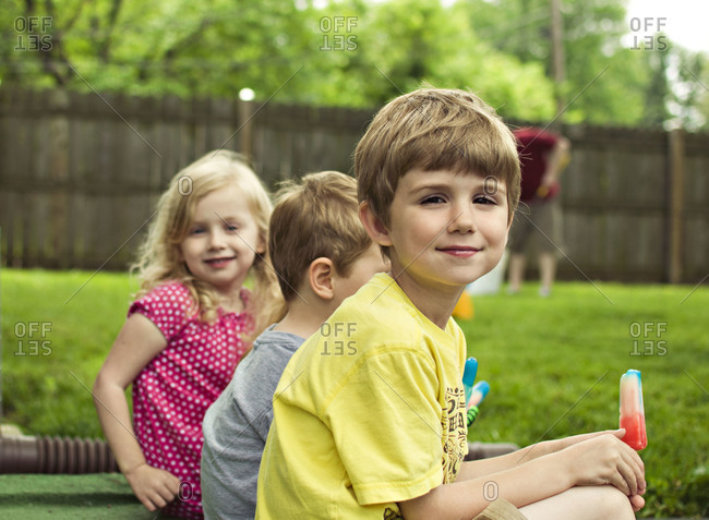 Boy in foreground with two other kids in background.  Boy smiling whileholding a ice pop.