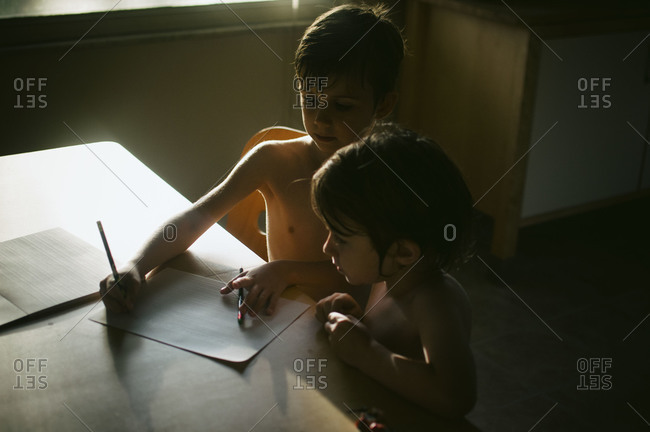 Two working on homework at the kitchen table.