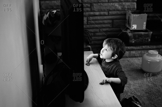 Young boy looking up at tv screen with the glow on his face.