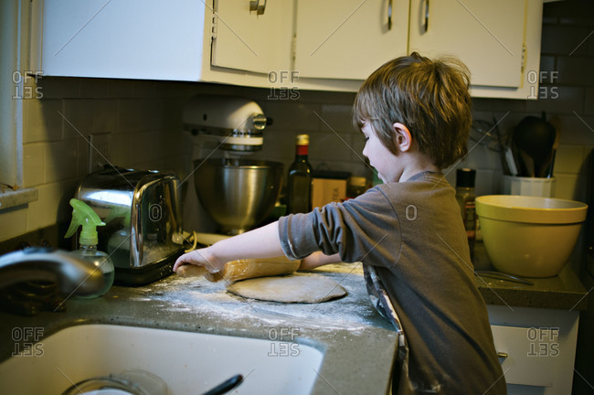 Boy rolling dough on kitchen counter