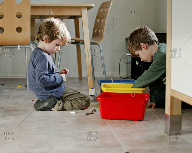 Brothers playing together in kitchen with colored bins