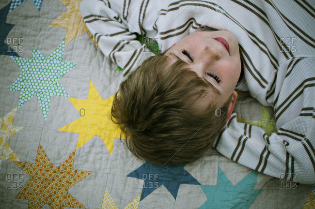Boy laying with hands behind his head on a quilt.  His eyes are closed
