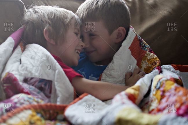 Boys wrapped up in quilt smiling at each other