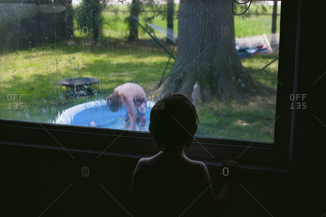 Young boy from inside watches another boy play outside in a swimmingpool.