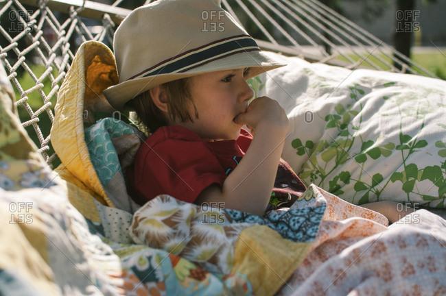Boy wearing a fedora resting in a hammock