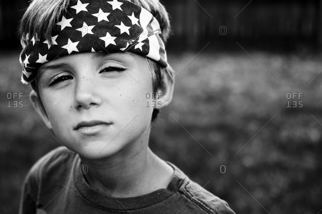 Boy wearing a stars and stripe bandana looking into the camera