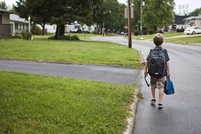 One boy walking to school with backpack and lunch bag.