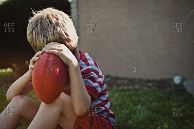 Boy holding a football over his face while sitting down