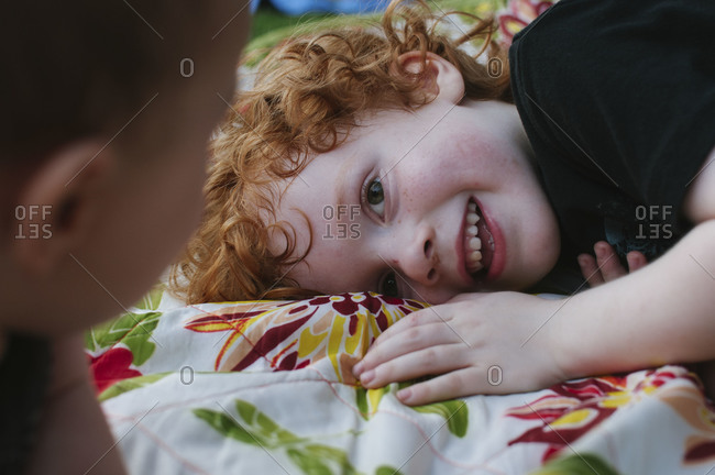 Red haired boy lays on quilt while smiling at an slightly off camera baby