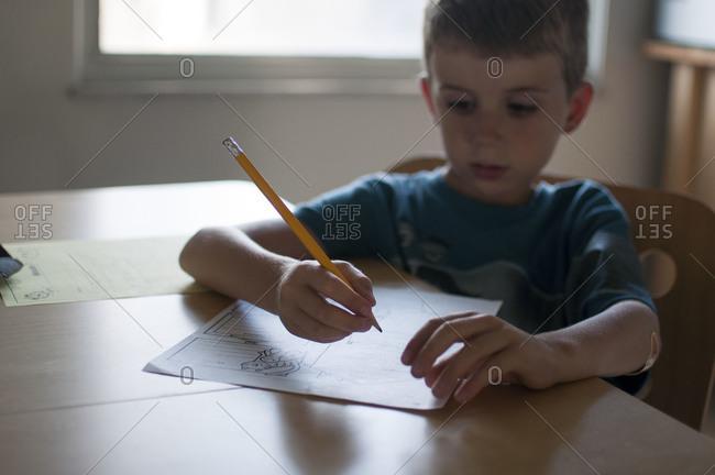 Boy doing homework at kitchen table.