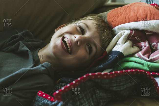 Young boy laying on quilt while laughing and smiling
