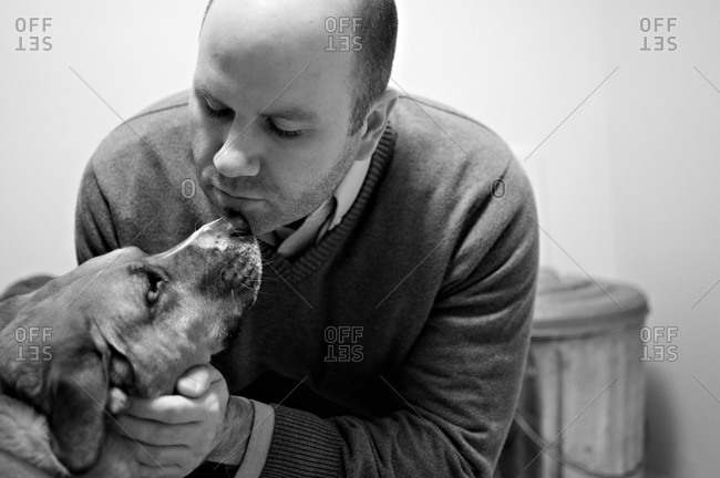 Man petting dog very close to his face