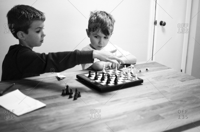 Two boys playing chess.  One making a move and the other one
