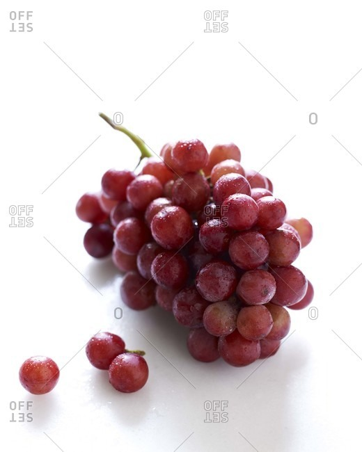 Red grapes on a white surface