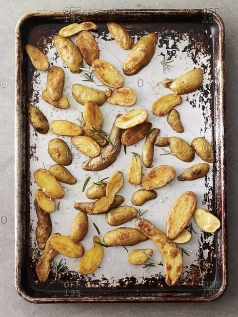 Roasted potato with rosemary in a baking sheet.