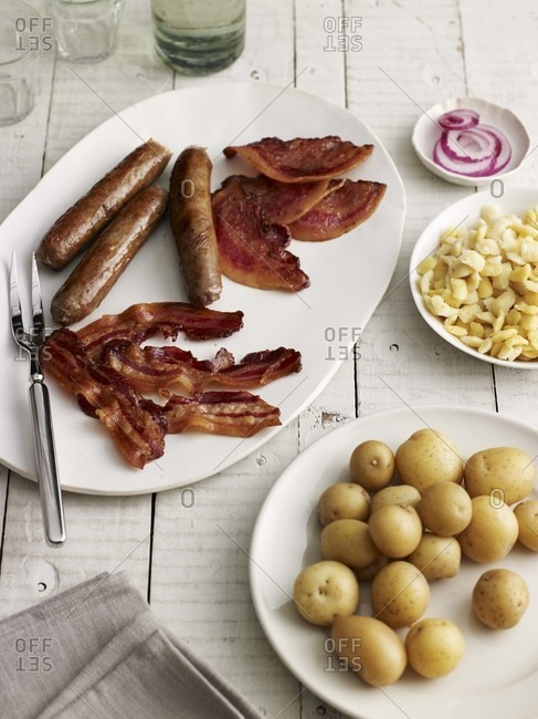 Sausages, bacon and sides on a white wooden table
