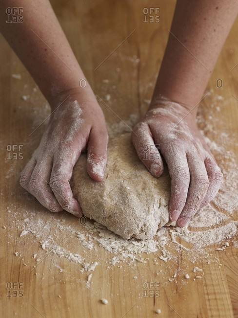Making pizza dough on a wooden surface
