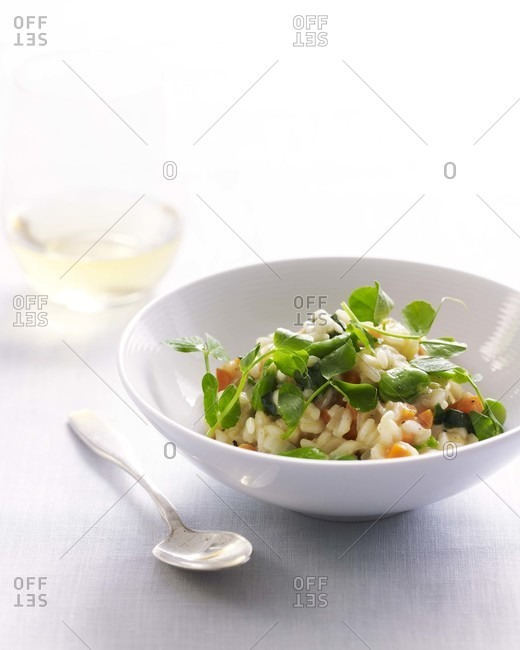Risotto with pea shoot in a white bowl with a spoon