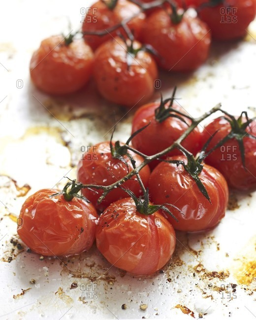 Roasted cherry tomato on a baking sheet.