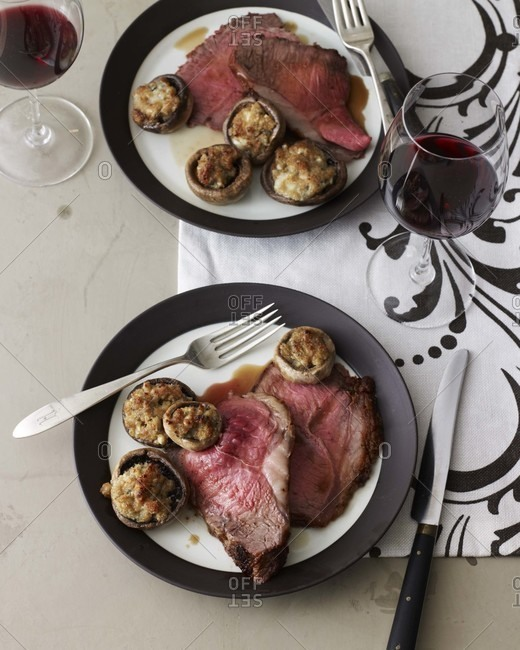 Sirloin Strip Roast with Roquefort Mushrooms on a table top.