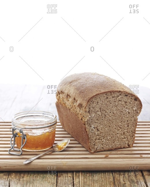 Whole wheat loaf and marmalade on a cutting board