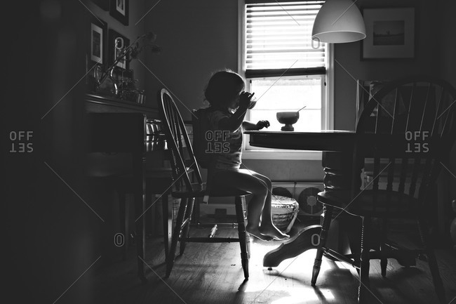 child sitting at table eating cereal