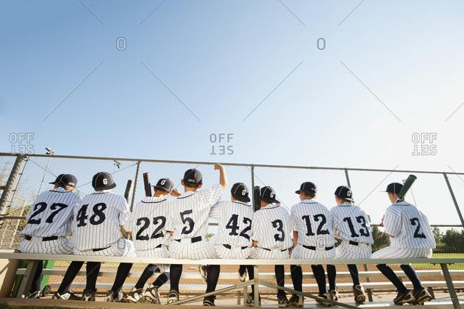 USA, California, Ladera Ranch, Boys (10-11) from baseball sitting on bench, rear view