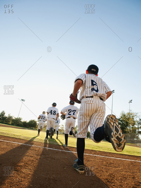 Baseball players (10-11) running on baseball diamond