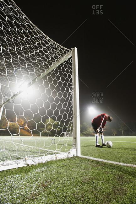 USA, California, Ladera Ranch, goalie on illuminated soccer field at night
