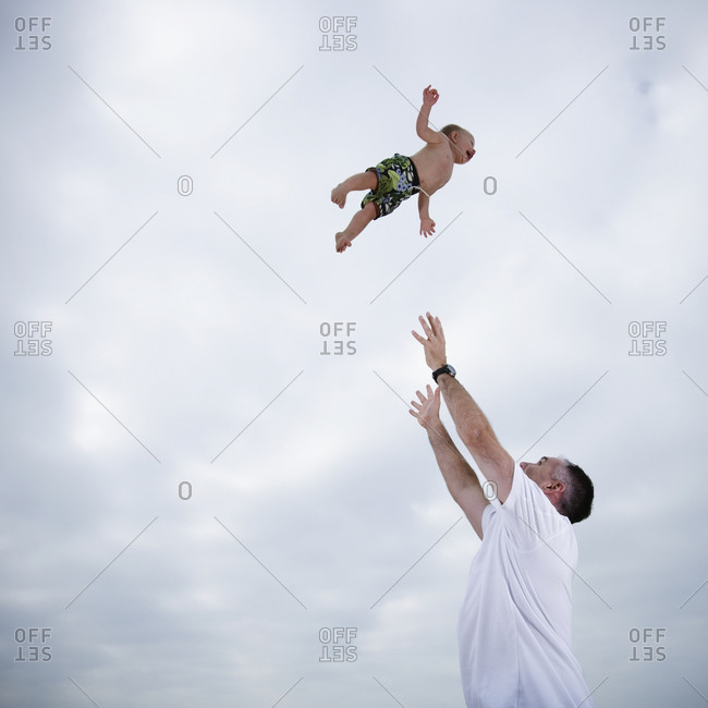 Father throwing young child in the air