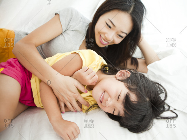 Mother with daughter lying down in bed, tickling (4-5)