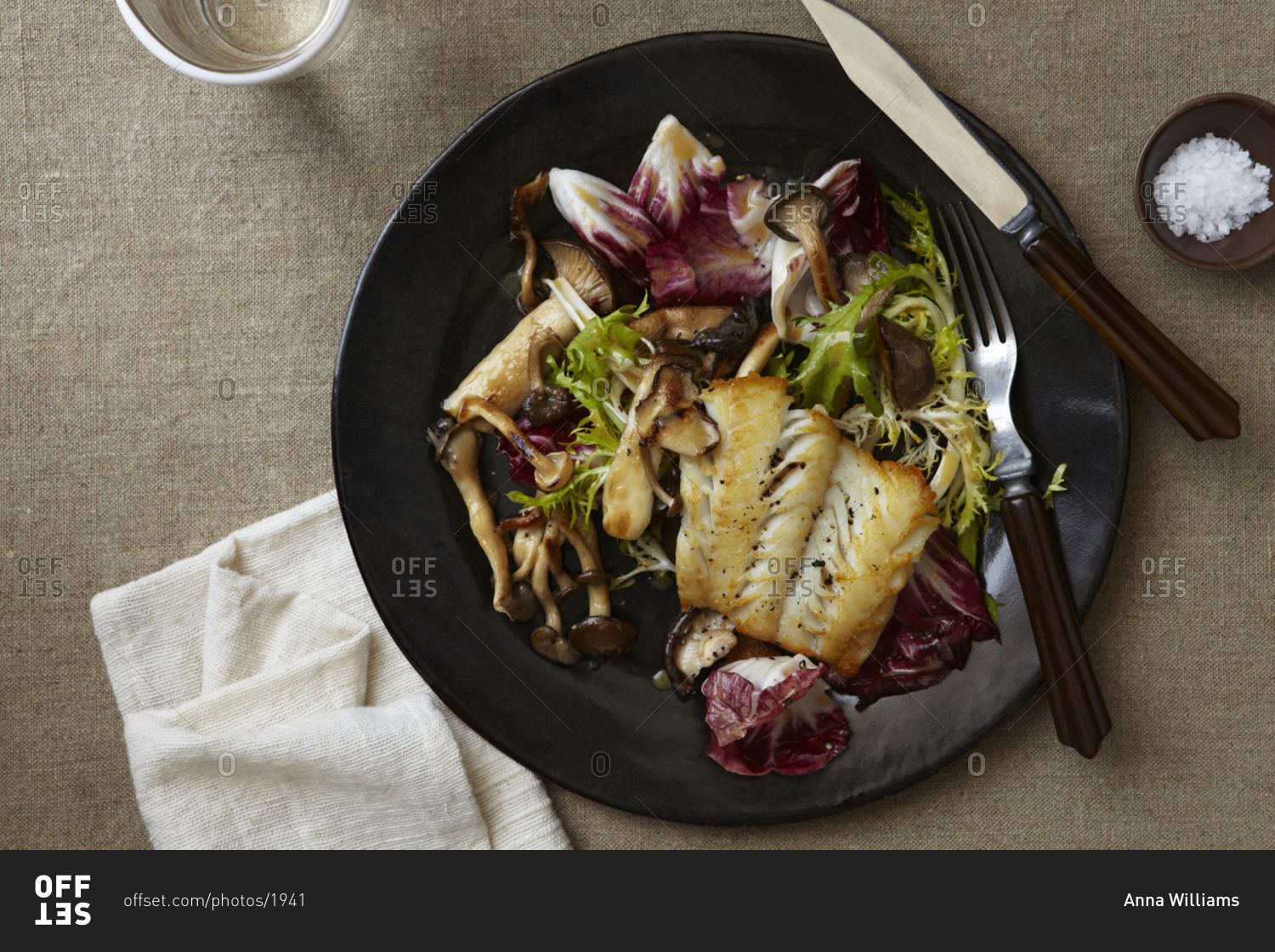 Roasted White Fish Fillet Meal With Radicchio Mushroom And Frisee In A Black Plate